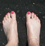 Beautifully manicured toes on the black sand beach of Hawaii.